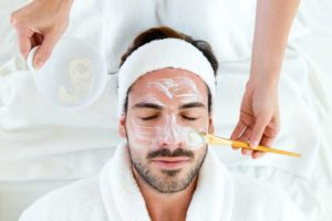 Man laying down getting a facial treatment