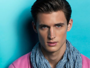 Male model Garrett Neff posing in front of a blue background wearing a scarf and a pink top